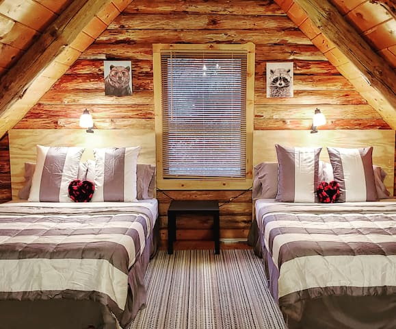 The upstairs loft bedroom with two queen beds and matching  cozy bedding.