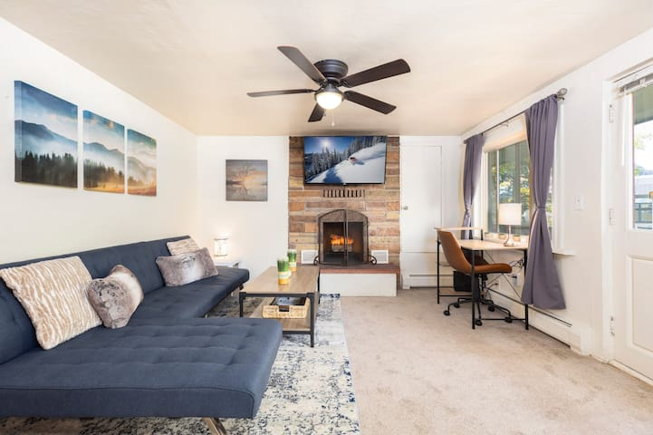 Living room with smart TV, wood burning fireplace, and desk/work area!