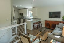 View of the entry stairs, kitchen, and living room w/ sleeper sofa.  Smart TV with HD antenna.