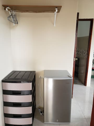There's an area to hang and store your clothes as well as a tall mini fridge with a small internal freezer.