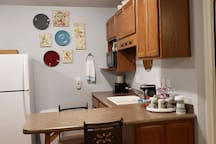Kitchenette with a microwave, full size refrigerator, induction countertop stovetop with pan, pod coffee maker & fixings, dishes, silverware, toaster, and a few snacks to keep you going!