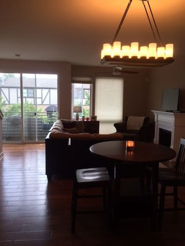 View of common living space from kitchen including electric fireplace, ceiling fan, TV, and balcony.