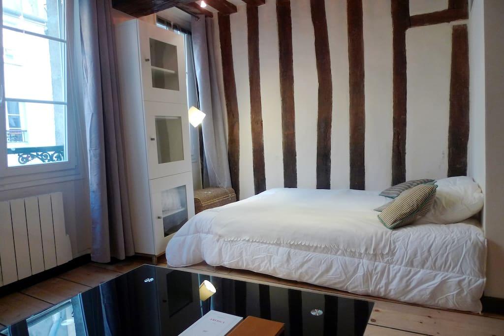 Apt. Descartes - Paris - Bed by one of the two windows, wooden floor & beams