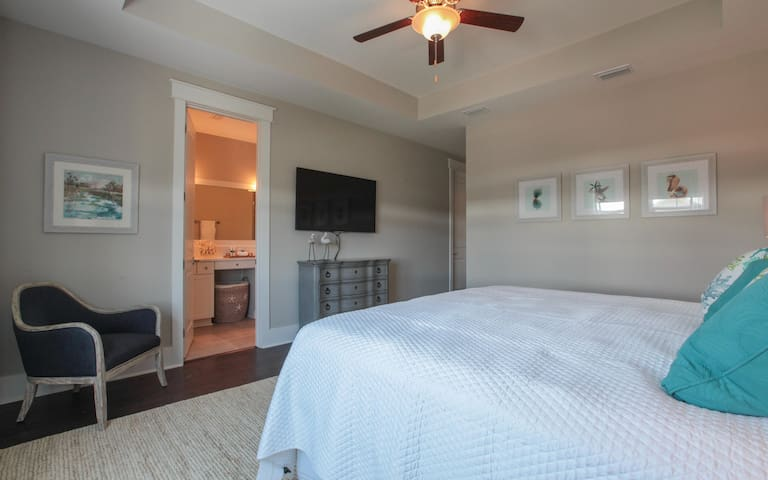 "master bedroom with private bath and 55"" tv"