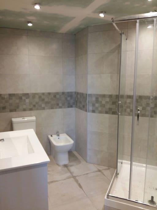 first bathroom with shower cabin primer baño con ducha