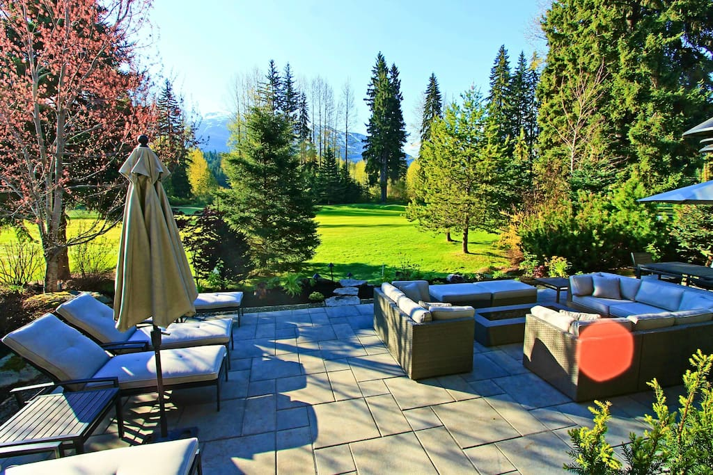 Backyard patio with firepit, sectional seating and chaise lounges