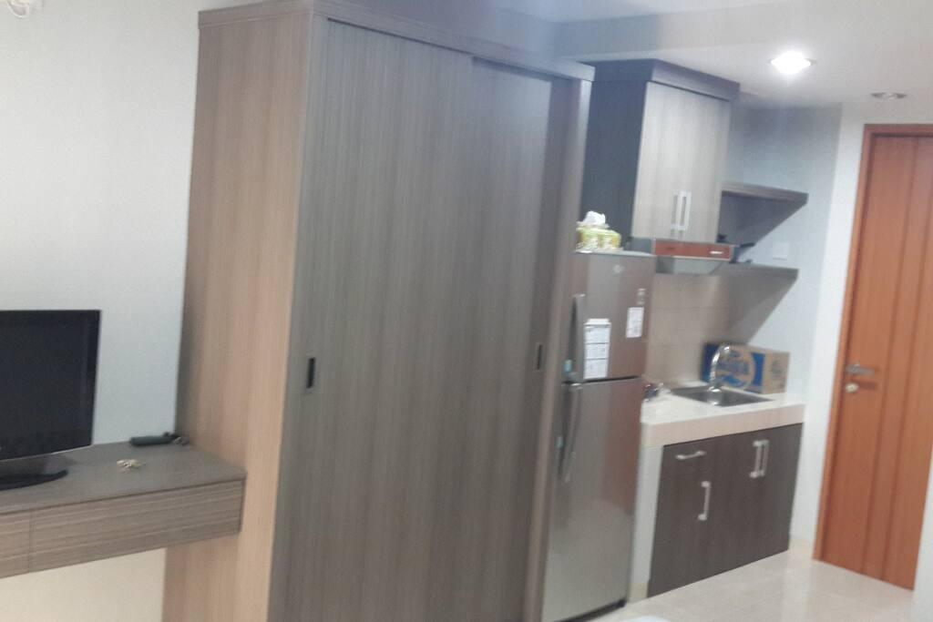 spacious closet alongside kitchen with full-sized fridge