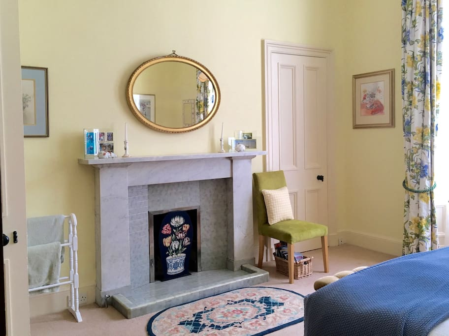 The room has traditional features such as a marble fireplace, gilt mirror and wall press.