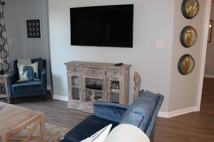 """50"""" flat screen tv in living room with viewing from kitchen and dining area."""