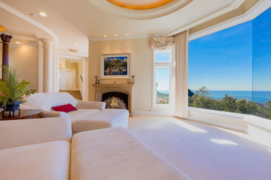 Master bedrooms comfy seating area with floor to ceiling views, fireplace, and terrace access.
