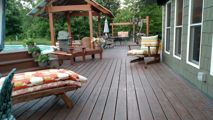 Entertainment area with gas grill outdoor speakers plenty of seating & swing. New pond not shown in this photo.