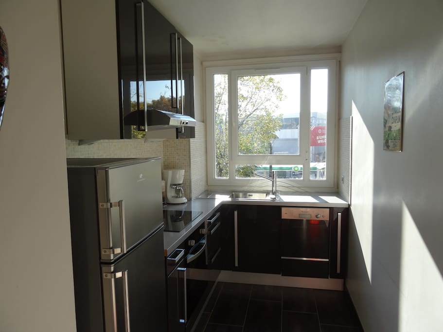 The 7 square meters separated kitchen has a double glazed window facing street . It is equipped with : fridge, freezer, dishwasher, ceramic hob, extractor hood, oven, microwave, coffee maker, kettle, toaster, and all kitchen utensils, tiled floor