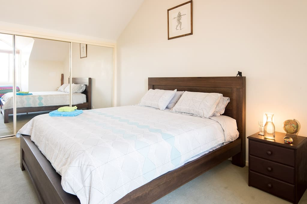 Top floor bedroom with comfortable, new king bed, new luxury bed linens, empty drawers and wardrobe space, mirrors, futon sofa, and a beautiful view over the Yarra Bend parkland