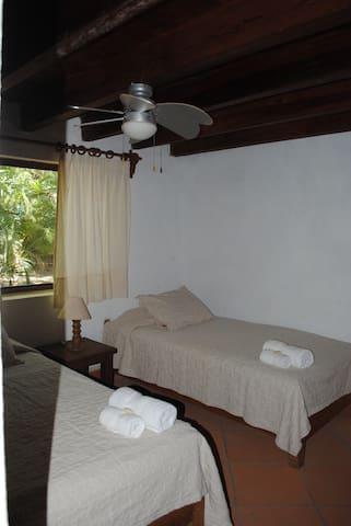 Dos camas individuales y ventilador de techo