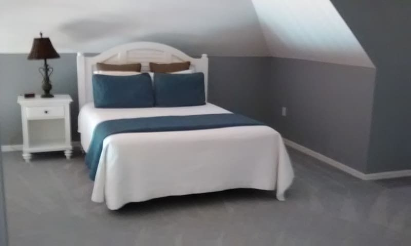 Bedroom in the loft done  up in blue and white