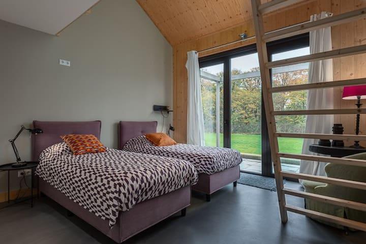 Slaapkamer 2 met twee eenpersoonsbeden en twijfelaar op de overloop.