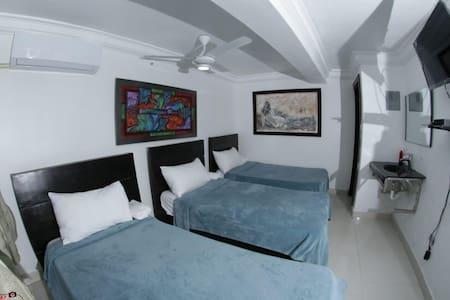 Habitación de cama triple con servicios de Aire acondicionado, wifi, televisión por cable,baño privado, ducha caliente.