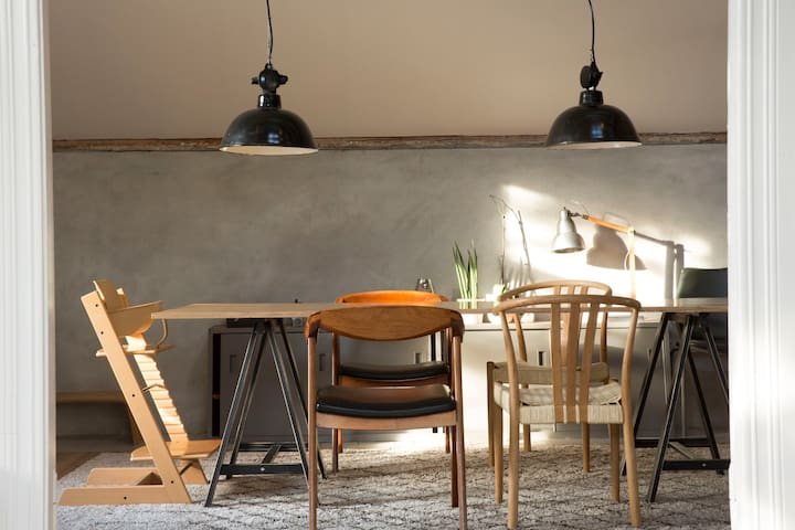 Cosy dining room with large plywood table, suitable for up to 8 people.