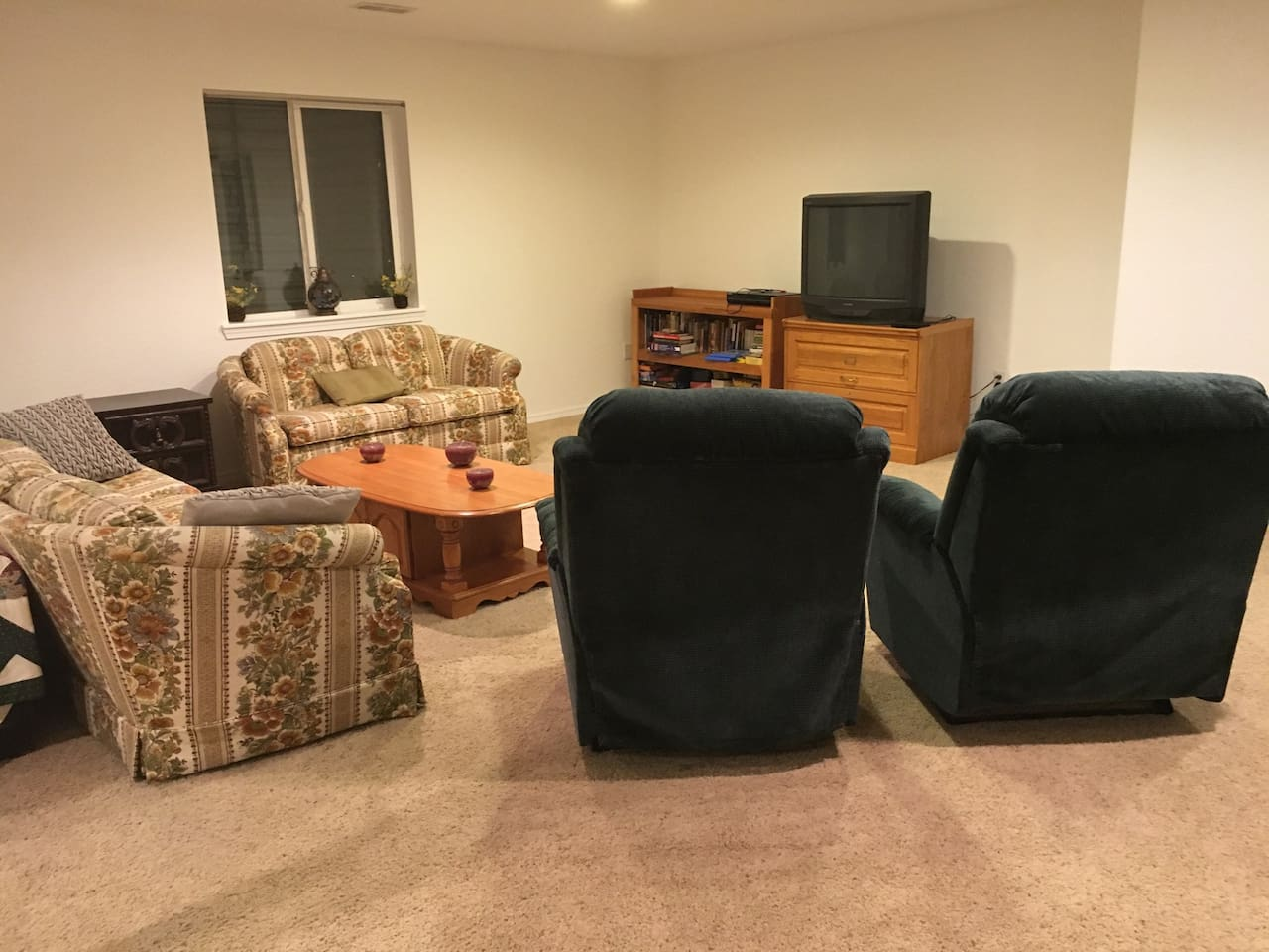 Living area has a couch, love seat, TV, games, books, and two recliners.