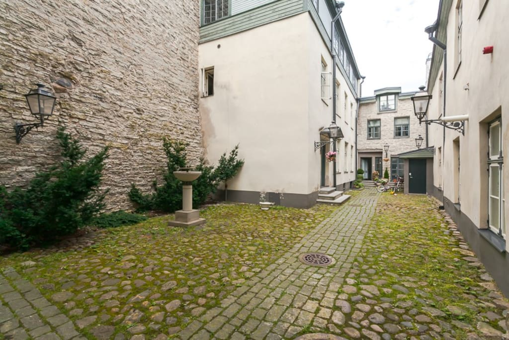 In the inner yard a fountain and the medieval city wall greet the guest.