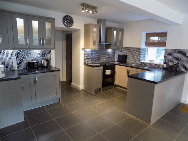 Open-plan kitchen with corridor leading to bedroom 1, bathroom, utility room and conservatory.