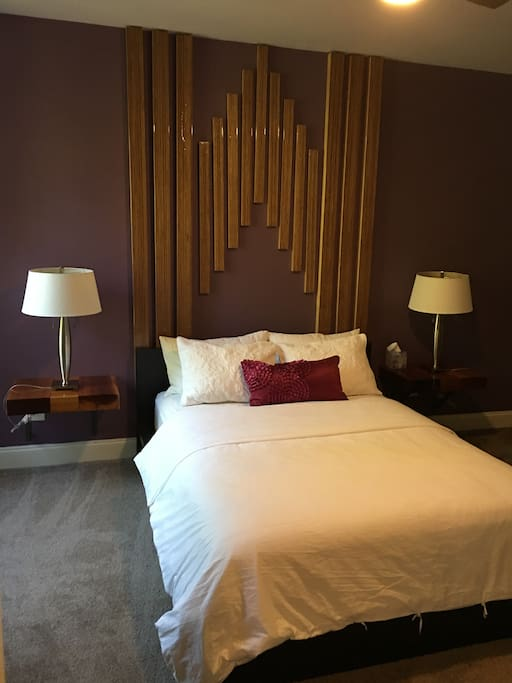 Queen size bed with beautiful art work throughout the apartment.