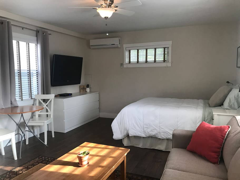 """45"""" TV with cable, blackout curtains, dresser, and AC/heat unit"""
