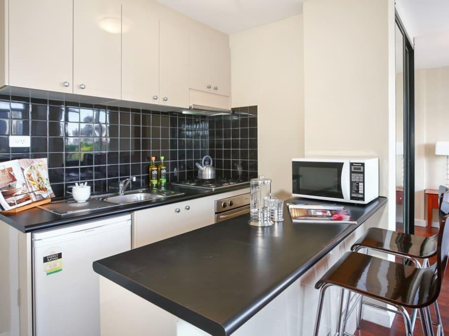 Sleek kitchen with gas range, oven, microwave and fridge