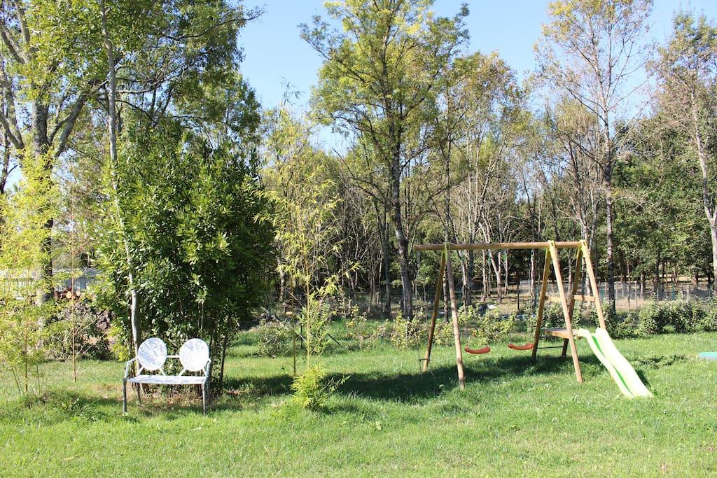 Jardin clôturé avec balançoire, bac à sable, cheval à bascule....