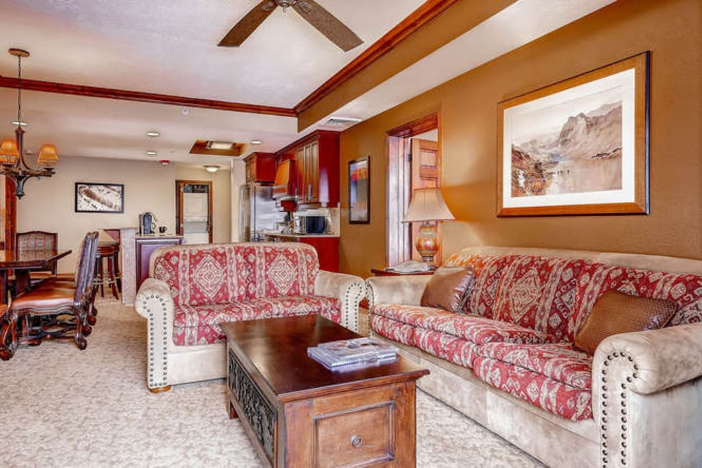 Spacious living room with fireplace, comfortable seating; facing gourmet kitchen with stainless steel appliances & dining room.