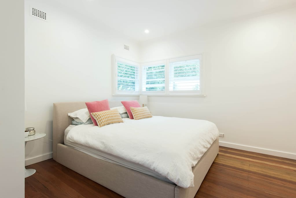 king size bedroom with plantation shutters and fly screens