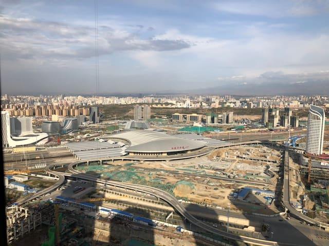 巨幕影院观景套房+第32层高楼的窗外+远眺雪山+将乌鲁木齐高铁站和城区尽收眼底
