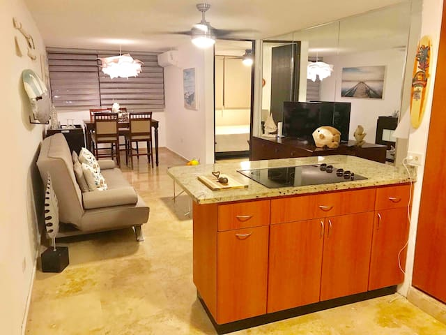 Ample open space living dining kitchen.  With air conditioning, ceiling fan, Smart TV with cable, sofa bed, Bar and dinning for four.