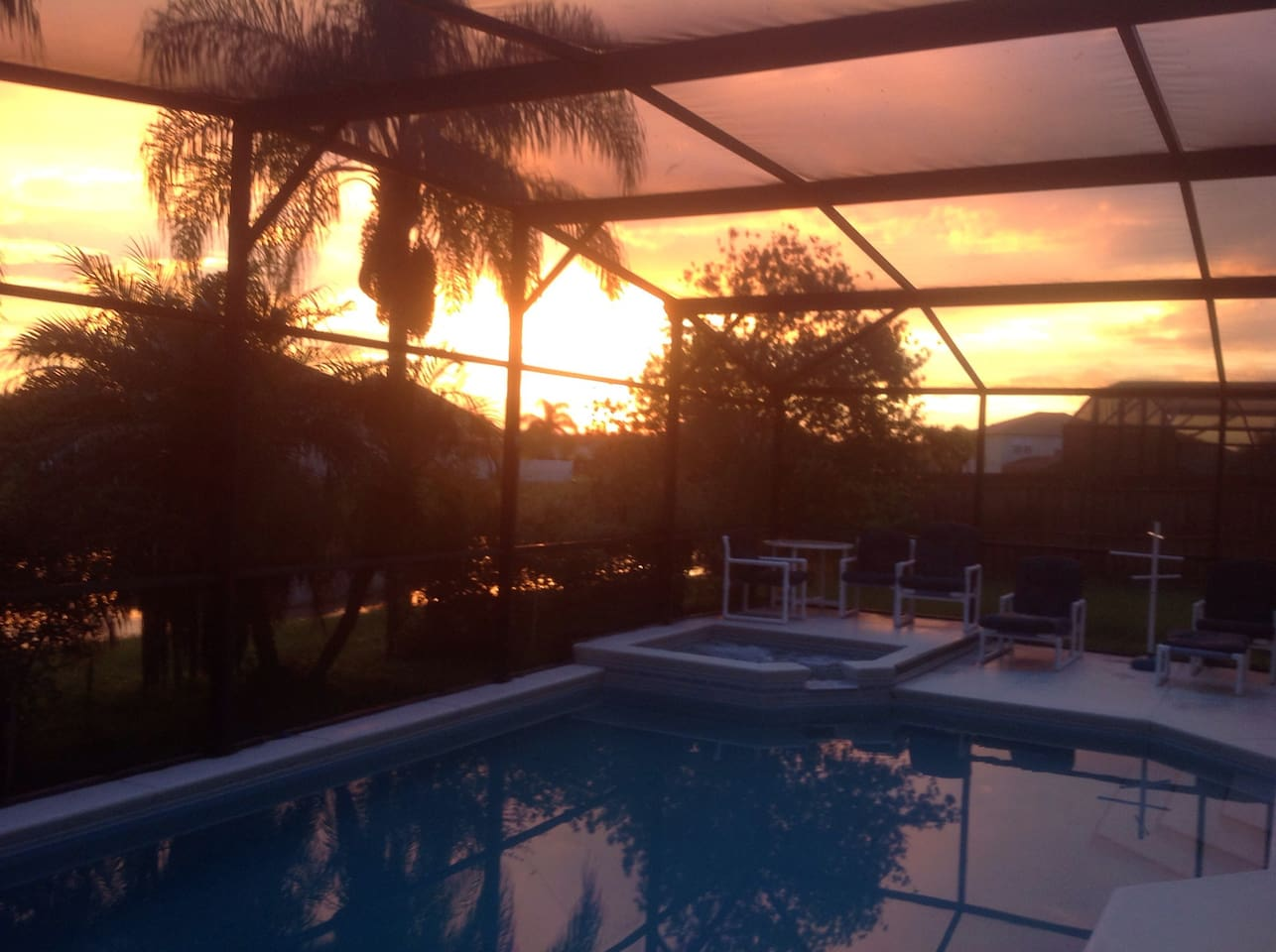 Sunset over the pool and spa within private gardens overlooking our lake