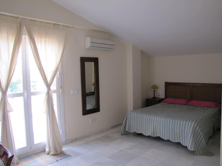 Dormitorio principal con baño y terraza.