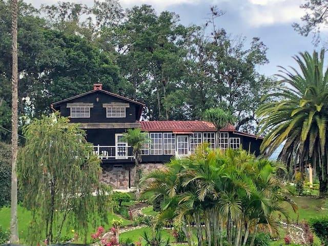 Casa entre un jardín cuidado con esmero y en lo alto de una plantación de café.