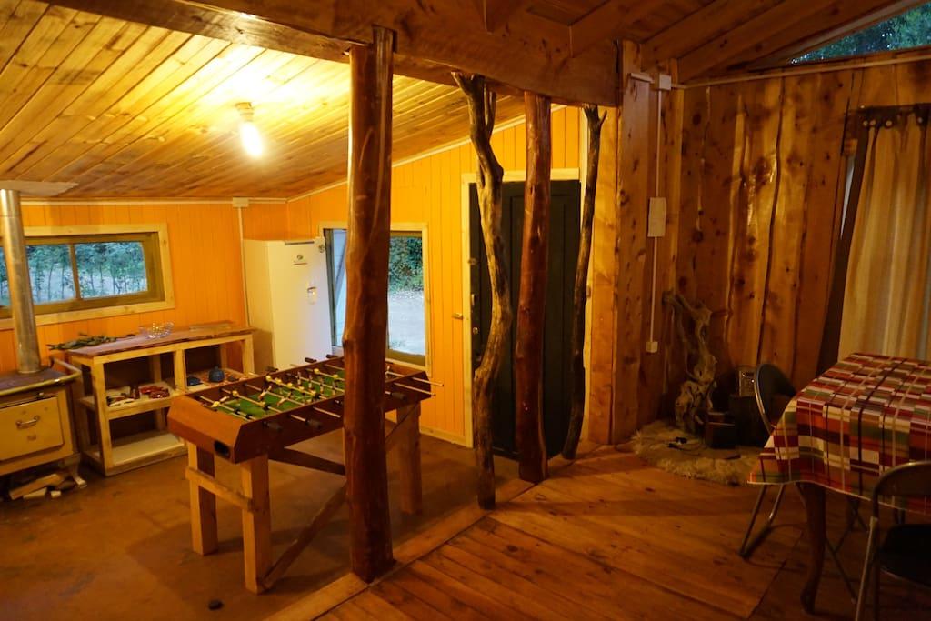 En la División entre el living y la cocina tenemos palos que hemos ido recogiendo del rio laja cada vez que viajamos  para allá. Hay una cocina a gas, muebles que estamos fabricando y un taca taca.