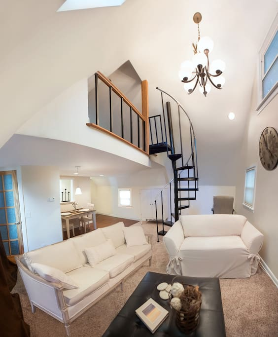 Living room with spiral staircase leading to loft.