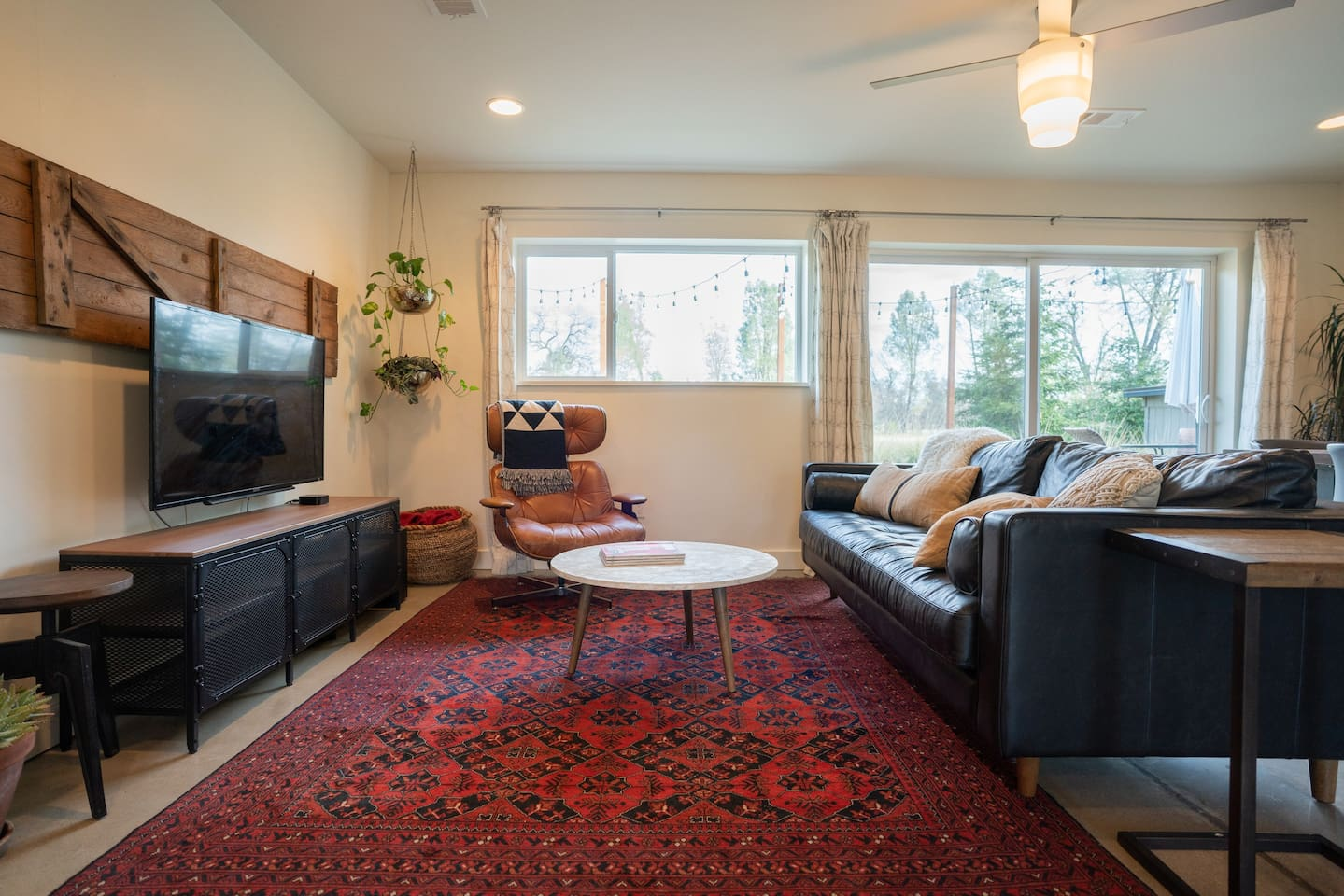 Comfort and style. Living area with antique Persian rug and eclectic furnishings.