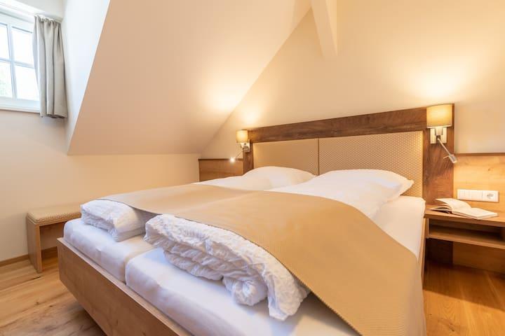Top 2 - Ferienwohnung Zirbenhäher, Schlafzimmer mit Doppelbett 180x200 cm, Schreibtisch, Smart TV und Garderobe mit Spiegel.