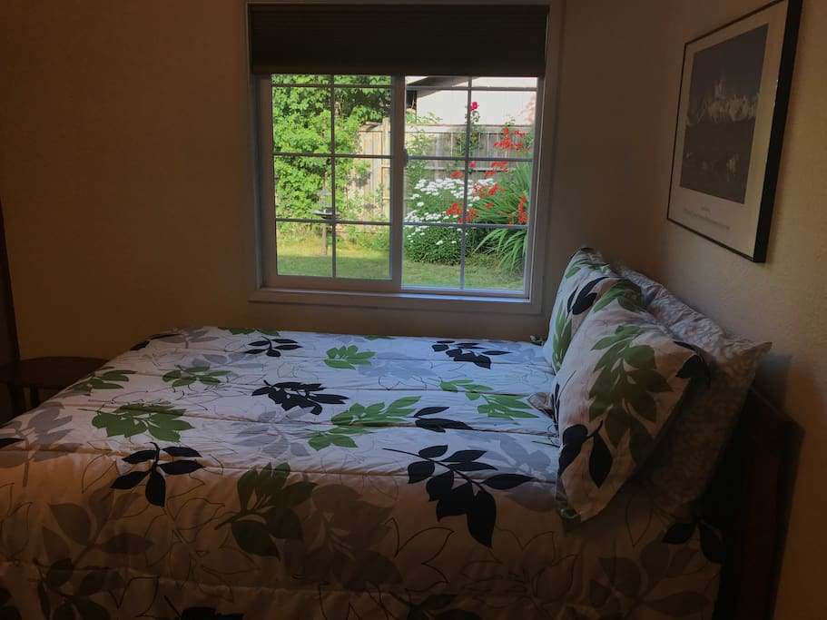 View of back yard through the window next to the bed. A room darkening window treatment is provided.