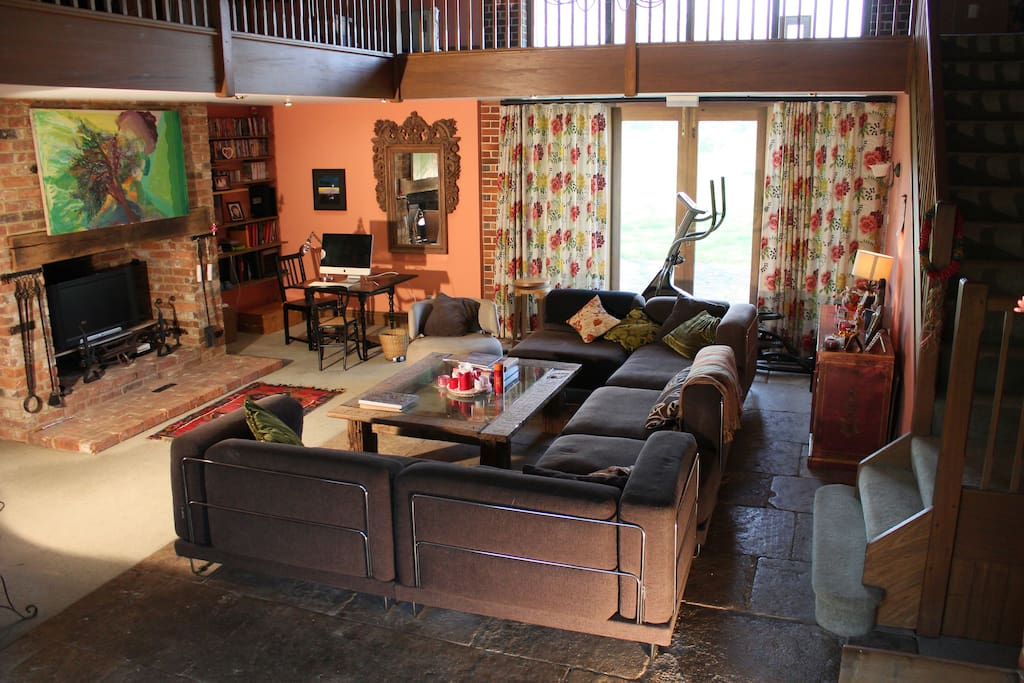 Comfortable and large double height large sitting room with vaulted ceiling and minstrels gallery with desk area and cross trainer with view to Cuckmere River