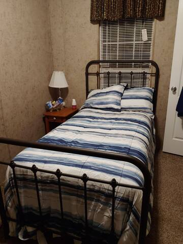 Small cozy room with twin bed, mini fridge, and tv