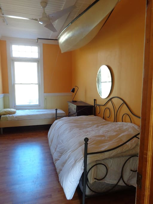 The kayak room has a trundle bed and a single bed with a kayak hanging overhead.