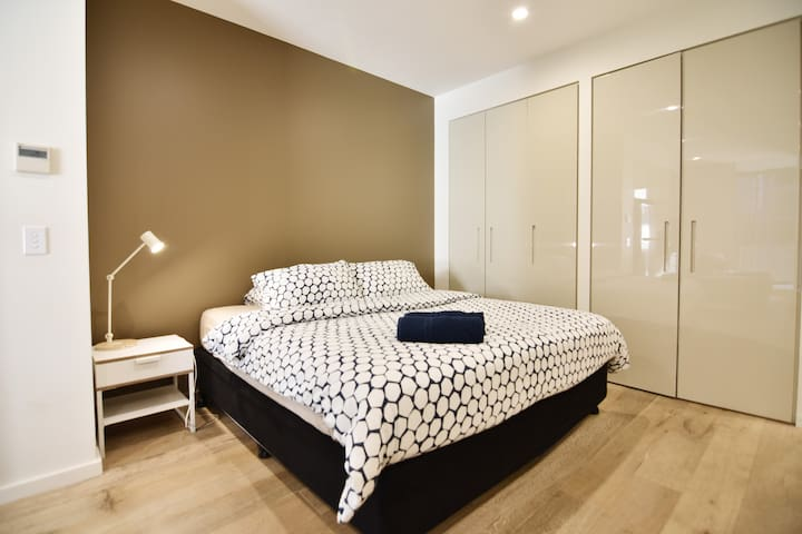 A bedroom area with a king sized bed & plush pillows.