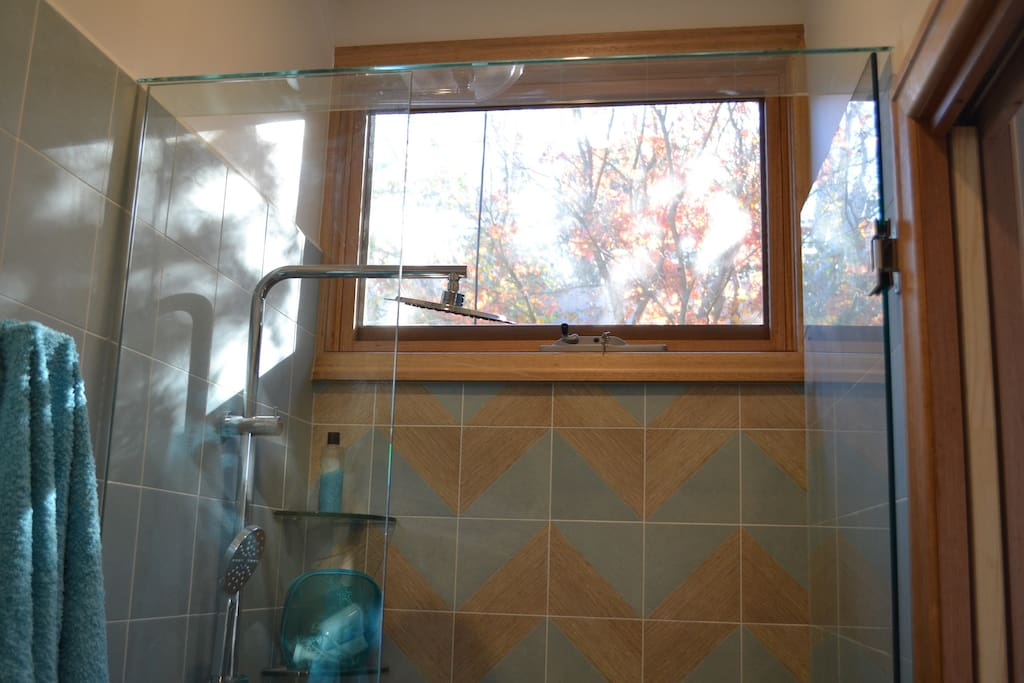 Contemporary tiles in the shower with an opening window.  Sun shines in during the winter months. Features: A rain shower, a hand held shower, an opening window.  Also Egyptian cotton towels, shampoo, conditioner, soap, hairdryer, shaving cabinet, mirror.