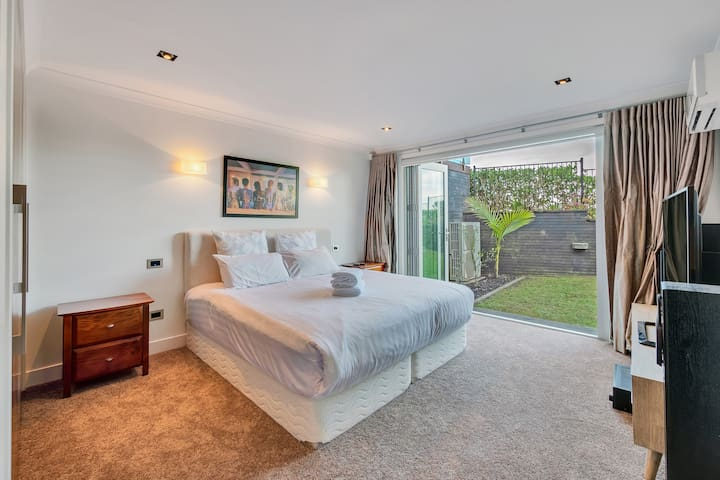 The ground floor bedroom with a super-king bed, garden view.  Bifold doors open to let in the ocean breeze and garden access. There is also access to the beach from this room.