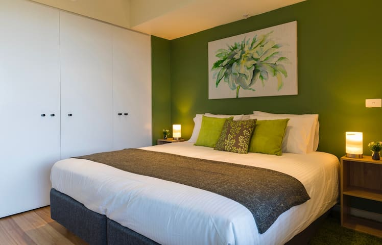 Small bedroom with king size bed - which can convert into 2 single beds. Brand new mattresses, hotel quality linen, doonas and pillows. Our pillow menu: low, medium and high profile. Plenty of storage space in the wardrobes.