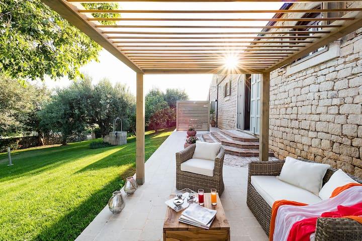 Bella villa di campagna con piscina privata a sfioro circondata da olivi.