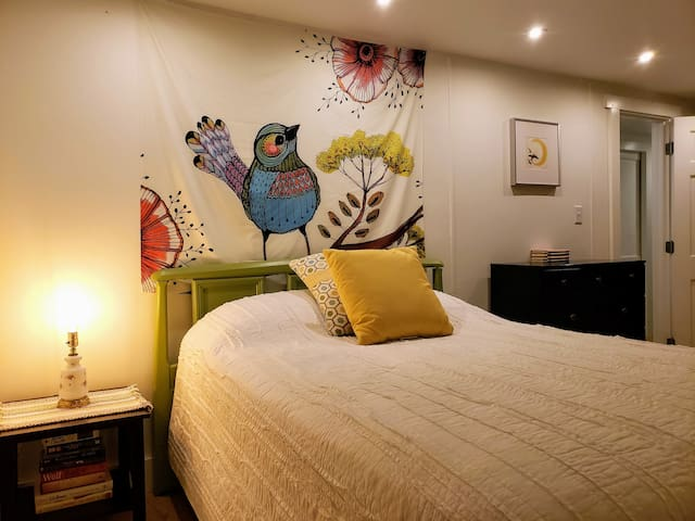 The bedroom gets a dose of color with a watercolor print tapestry.